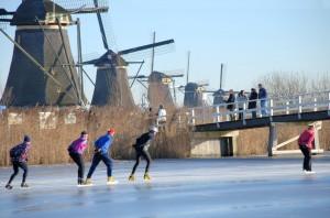 Schaatsers bij de molens van Kinderdijk